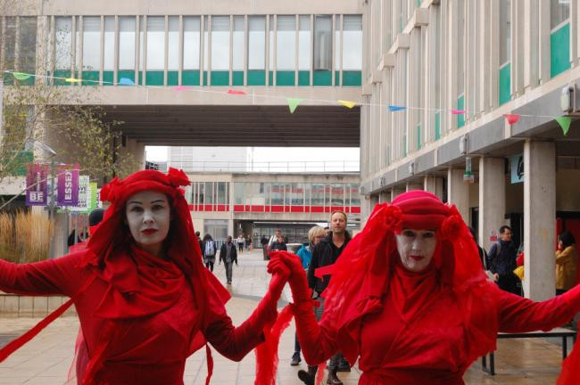 Protest - two protestors dressed in the red rebel brigade outfits at Essex University
