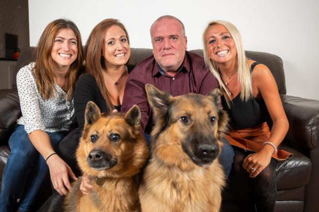 Paul Viner, 55 with daughters (L-R) Kealy Gulrajami, 33, Gemma Viner ,31 and Leah Bolt , 28, with German Shepard's Sheba age 7 and Sky age 2. See SWNS copy SWCAnest: A dad-of-three was left with empty nest syndrome after his adult daughters all left