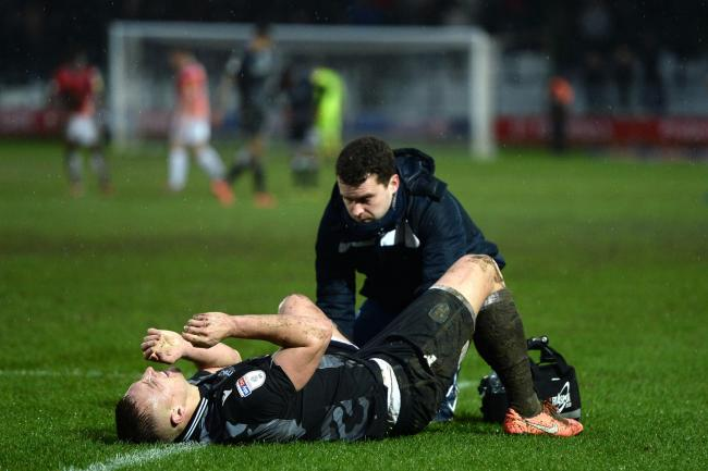Pain - Colchester United striker Luke Norris is treated by physio Shayne O'Reilly after picking up an ankle knock against Salford City Picture: RICHARD BLAXALL