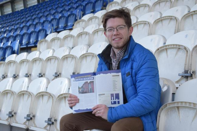 Combining his two passions - Steven Bishop, pictured at the JobServe Community Stadium with the programme for last month's home game against Plymouth Argyle. It features one of the history articles he has written for every home match programme this