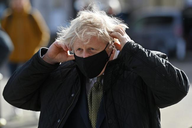 Prime Minister Boris Johnson puts on a mask