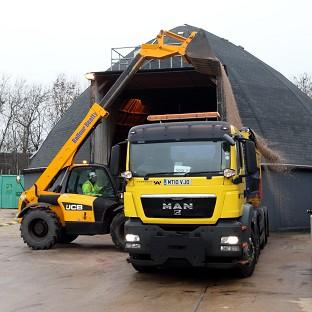 A Highways Agency worker loads gritting salt as weather forecasters predict snow across parts of the country