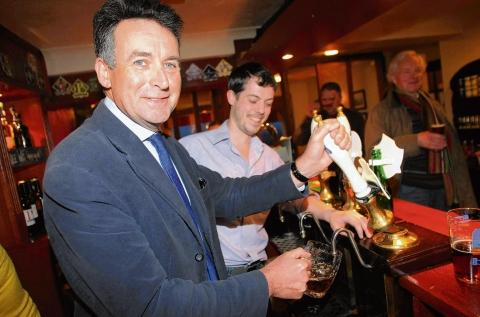 MP Bernard Jenkin takes his place behind the bar at Thatchers Arms in Bures to speak with landlord Mitch Adams.