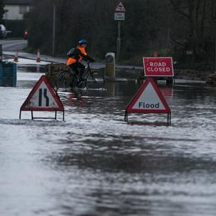 Halstead Gazette: A flooded road near Chertsey in Surrey as large swathes of England and Wales are on flood alert