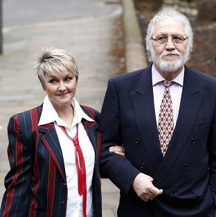 Halstead Gazette: Former disc jockey Dave Lee Travis arrives at Southwark Crown Court with his wife Marianne.