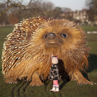 Bodhi, three, looks up at a model of a hedgehog on Clapham Common in London to mark the launch of Sir David Attenborough's Natural Curiosities