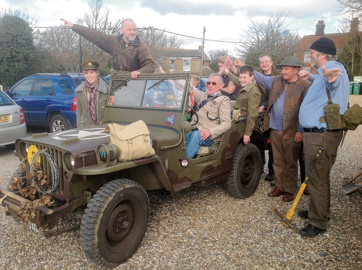 Wartime vehicles go on convoy through village