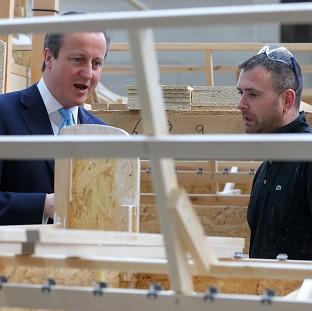 Halstead Gazette: Prime Minister David Cameron talks to frame assembler Darren Jones during a visit to Westbridge Furniture Ltd, a sofa manufacturers in Greenfield, North Wales