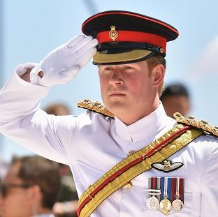 Halstead Gazette: Prince Harry salutes after laying a wreath on behalf of The Queen during a commemoration service at Monte Cassino cemetery