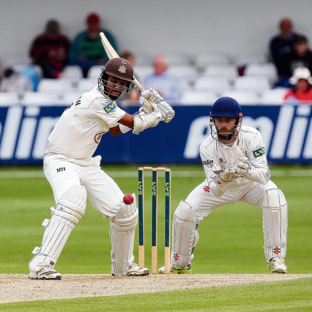 Halstead Gazette: James Foster looks on as Arun Harinath hits out for Surrey
