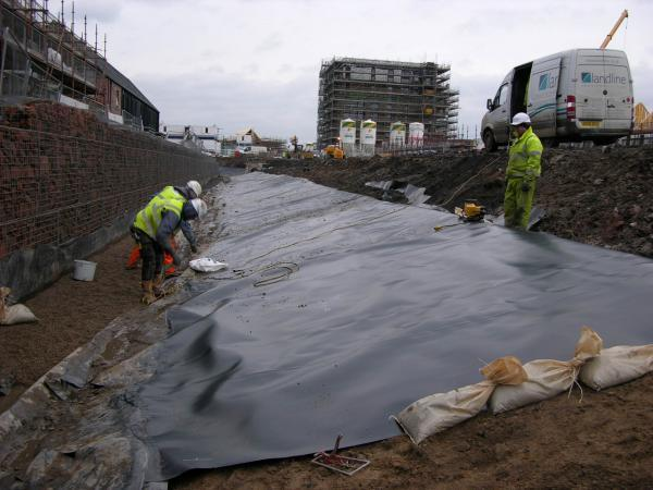 Landline Ltd working at the Athlete's Village, lining a decorative canal.