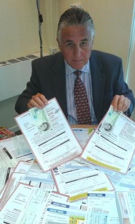 Roger Walters with some of the cash and cheques to be returned to Essex residents who fell for a prize draw and confectionery scam.