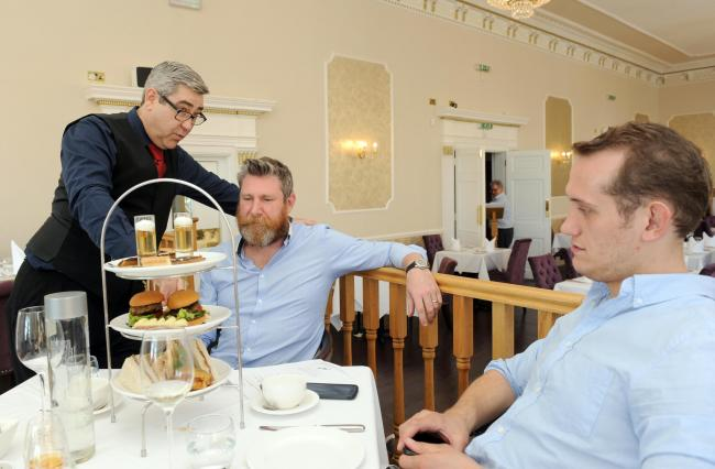 Gentleman's afternoon tea at the Royal Hotel, high street, southend.Maitre D Jonathan Peters serving the afternoon tea to Matthew Courtier ( beard) and Rob Gibson.